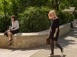 Two girls in a world of their own in the City of London on a sunny day.