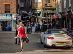 Girl in red top walking in Shepherd Market Mayfair London UK, on an evening in Spring